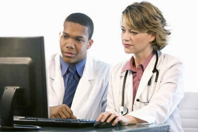 Two docs at laptop looking left.jpg